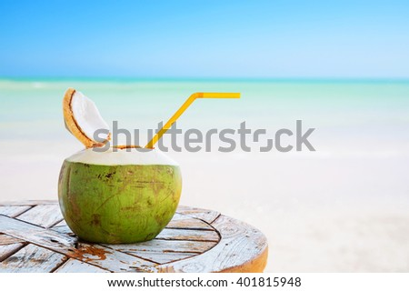 Coconut juice with straw on wood table against blurred beach background. - stock photo