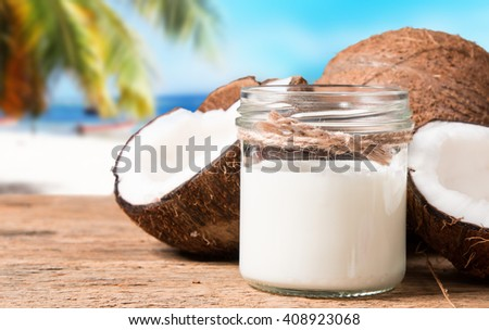 coconut milk and fresh coconuts on old wooden table with tropical beach background - stock photo