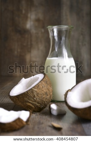 Coconut milk in a vintage bottle on rustic wooden background.