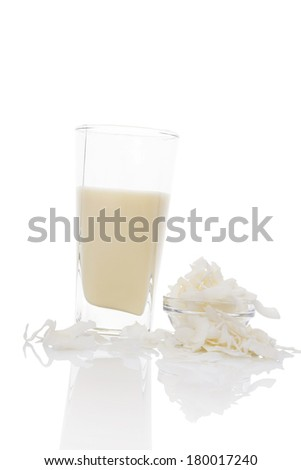 Coconut milk in glass with coconut flakes in glass bowl isolated on white background. Vegan and vegetarian milk concept.