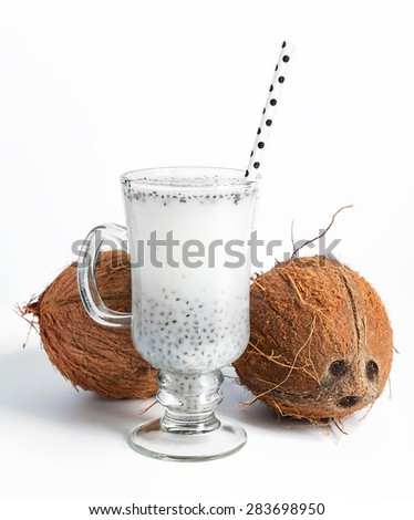 Coconut milk with chia seeds served in glass with white paper polka dot straw. Cold and refreshing drink. On white background. Selective focus. - stock photo
