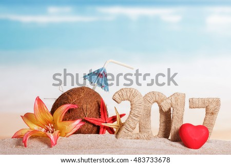 Coconut, number 2017, starfish, flower and heart in the sand on the sea background.