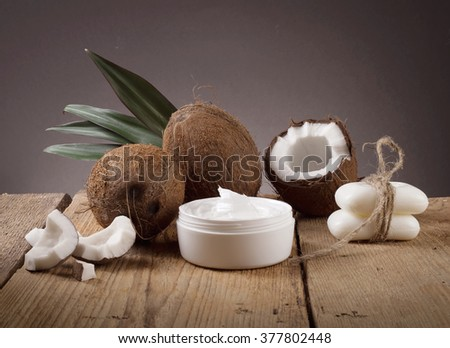 coconut oil and fresh coconuts on old wooden table - stock photo