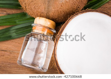 coconut oil in a bottle, background is a half of coconut and leaf on the wooden table - stock photo