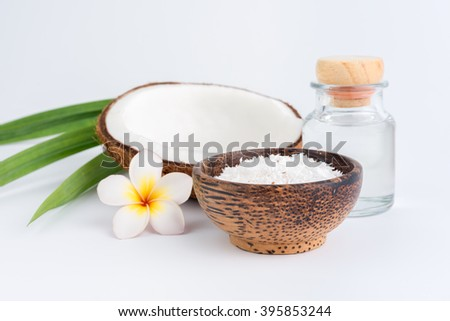 coconut oil in a bottle, background is a half of coconut, isolated - stock photo