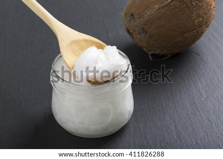 Coconut oil in a glass jar on a black  - stock photo