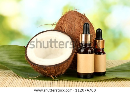 coconut oil in bottles with coconuts on green background - stock photo