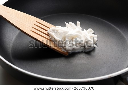 Coconut oil in frying pan close up - stock photo