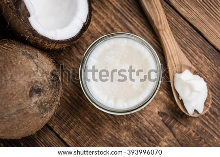 Coconut Oil (selective focus) on an old wooden table (close-up shot) - stock photo