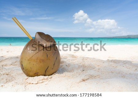 coconut on a white sandy beach with a straw in it on a turquoise ocean background on a sunny day