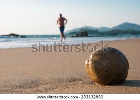 Coconut on the beach and the running man - stock photo