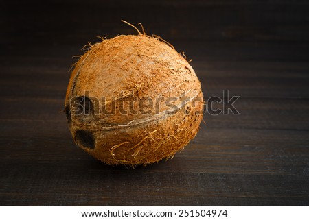 Coconut on the old dark boards - stock photo