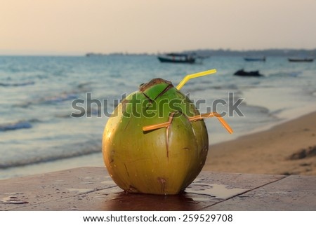 Coconut on the wooden table on beach at sunset view 3 - stock photo