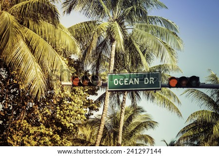 Coconut palm trees against Ocean Drive sign in Miami Beach, Florida - stock photo