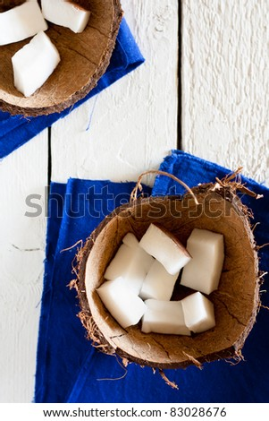 Coconut Pieces in a Shell, with Blue Napkin on White Wood - stock photo