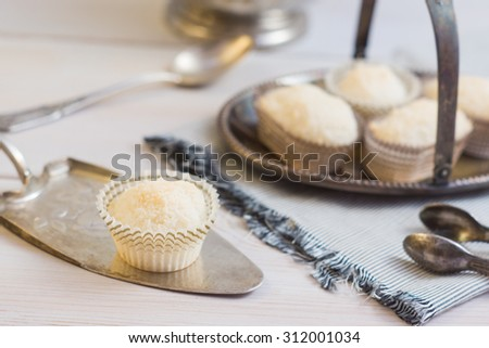 Coconut protein cupcake sweets in a paper pack on a silver plate with silver spoons and tongs on a grey napkin on a dark grey wooden background