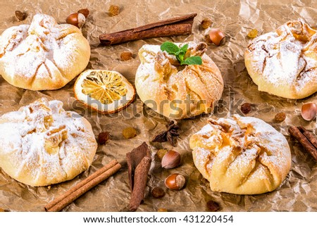 coconut puff pastries on parchment paper sprinkled with sugar icing, close up - stock photo