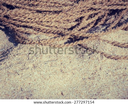 Coconut rope on  sand close up. Toned effect - stock photo
