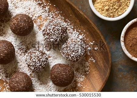 Coconut rum balls being covered with grated coconut, ingredients (cocoa powder, ground cookies) on the side, photographed overhead with natural light (Selective Focus, Focus on the top of the balls)