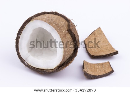 Coconut sliced in halves both with and without the coconut meat on white background.
