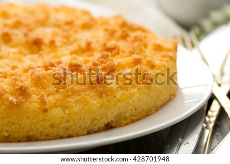 coconut tarte on brown dish in white wooden background with forks