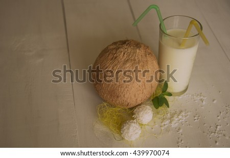 Coconut together with glass of milk and nice tiny candies