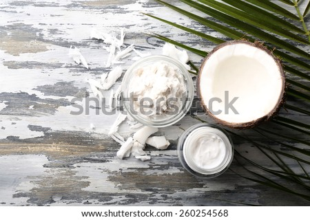 Coconut with coconut oil in bowl with jar of cosmetic cream on wooden background - stock photo