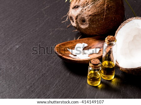 Coconut with coconut oil in jar on black background