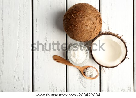 Coconut with coconut oil in jar on wooden background - stock photo
