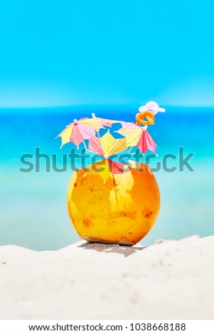 Coconut with colorful umbrellas and straws on a beach, summer fun holiday concept, selective focus.