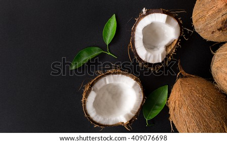 Coconut with green leaves isolated on a black background. Broken coconut. top composition