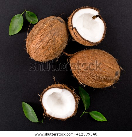 Coconut with green leaves isolated on a black background. Broken coconut. top composition - stock photo