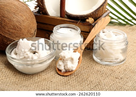 Coconut with jars of coconut oil and  cosmetic cream on sackcloth background - stock photo