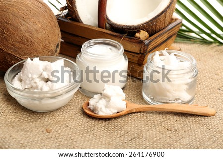 Coconut with jars of coconut oil and  cosmetic cream on sackcloth on natural background - stock photo