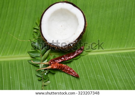 Coconut with Kashmiri chilli/chilly, curry leaves on a banana leaf top view .Used in cooking, frying,seasoning for sambar, chutney. coconut oil is used in soaps, cosmetics. red chilly Kerala India .  - stock photo