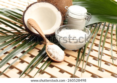 Coconut with leaf and coconut oil in jar on wooden background - stock photo