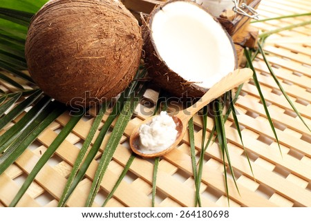 Coconut with leaf and coconut oil in spoon on wooden background - stock photo