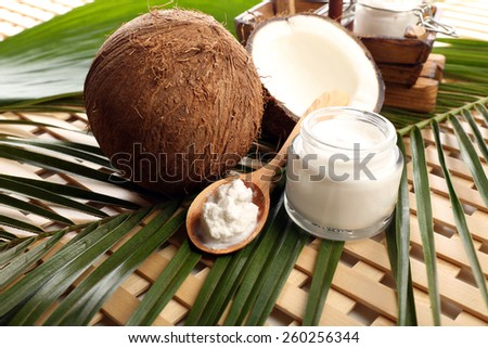 Coconut with leaf and cosmetic cream in jar on wooden background