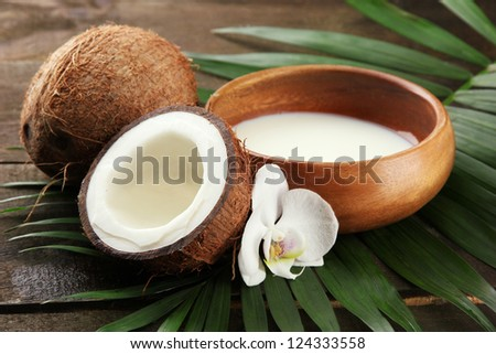 Coconut with leaves and flower, on grey wooden background - stock photo