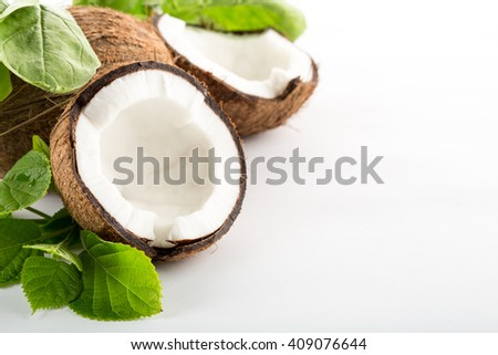 Coconut with leaves isolated on white background. Space for text on the right. - stock photo