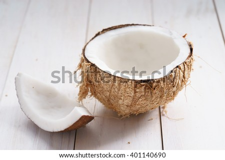coconut with shell on white wooden background - stock photo