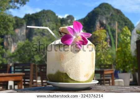Coconut with straw and a flower on a table in Thailand - stock photo