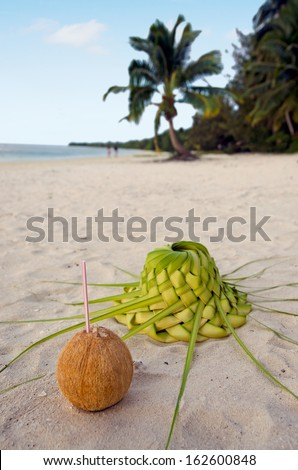 Coconut with straw and sun hat knees out of palm leaves with couple of tourists in the background  on sandy sea shore of tropical island. - stock photo