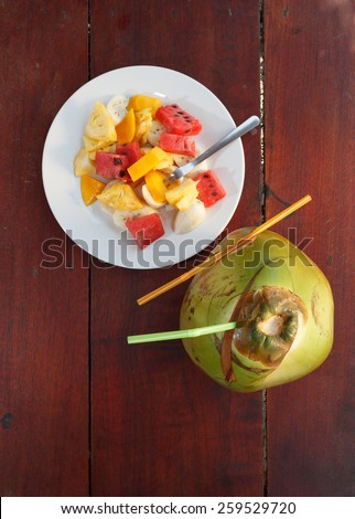 Coconut with straws and fruit salad on the wooden table top view 2 - stock photo