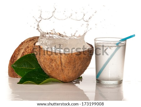 Coconut with water splash over white - stock photo