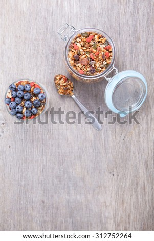 Coconut yogurt topped with grain free paleo granola made with mixed nuts, seeds, raisins, with blueberries on the top, above view - stock photo