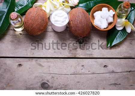 Coconuts,  coconut oil and milk on  vintage wooden background. Selective focus.  Natural organic spa products. Place for text. 