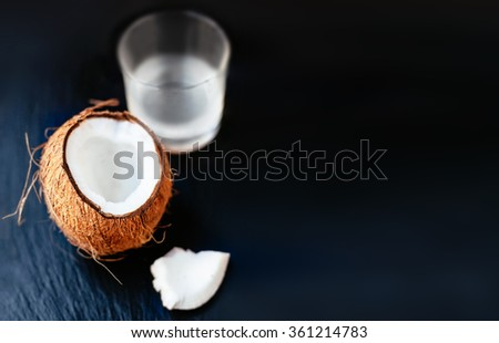 Coconuts with milk. 		Coconut with coconut milk in a glass on dark  background with copy space