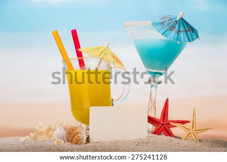 Coctails in the glasses, blank paper and starfishes in the sand - stock photo