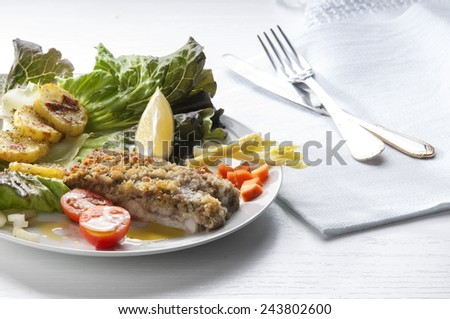 cod fillet breaded and baked with potatoes and salad as garnishing - stock photo